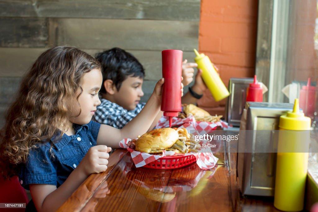 Mixed race children having burgers in restaurant : Stock Photo