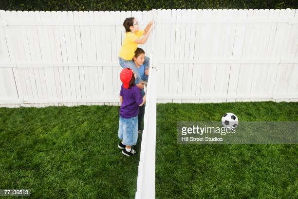 Mixed Race children looking over fence at soccer ball