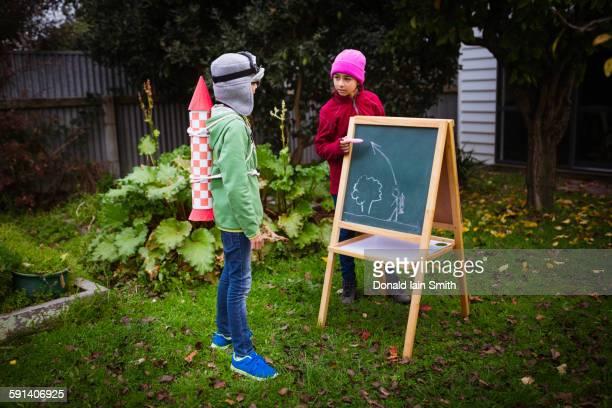 Mixed race children planning jetpack rocket