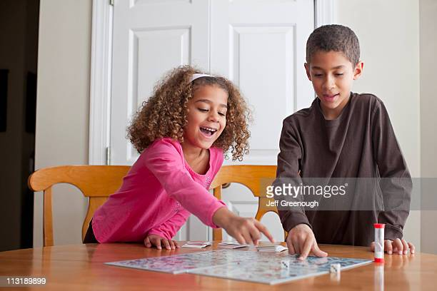 mixed race children playing board game together - game board stock photos and pictures