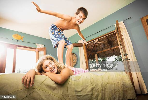 Mixed race children playing on bed