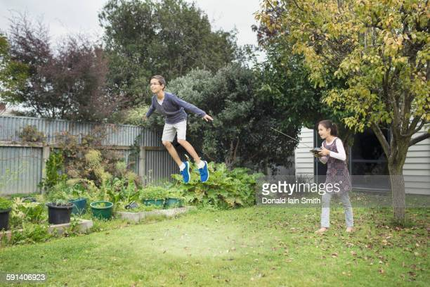 Mixed race children playing with hover toy in backyard