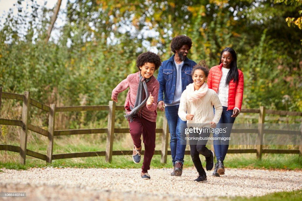 Mixed race children running ahead of their parents on a path during family walk in the countryside, low angle : Stock Photo