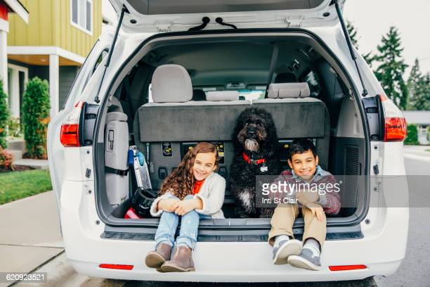 Mixed race children sitting with dog in car hatch