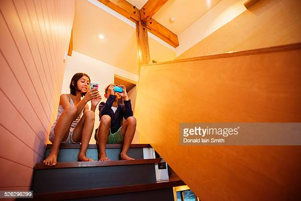 Mixed race children using cell phones on staircase