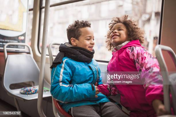 Mixed race children with mother traveling by tram