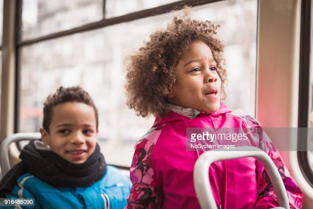 mixed race children with mother traveling by tram - multiculturalism stock pictures, royalty-free photos & images