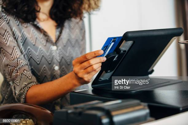 mixed race clerk swiping credit card at register - credit card reader stock pictures, royalty-free photos & images