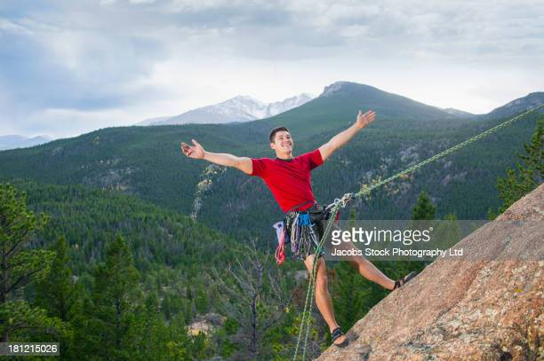 Mixed race climber hanging from steep rock face