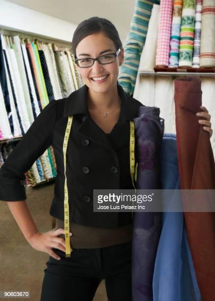 Mixed race clothing designer holding fabric