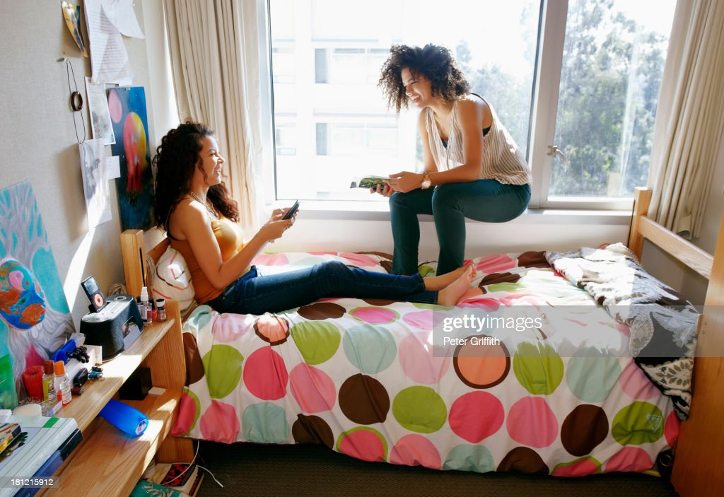 Mixed race college students relaxing in dorm : Stock Photo