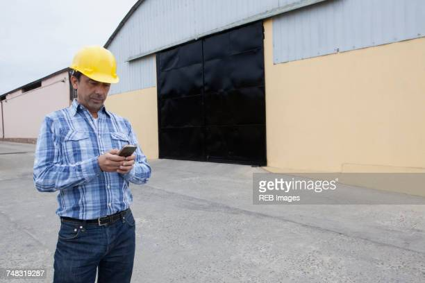 Mixed Race construction worker texting on cell phone