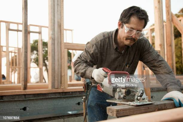 mixed race construction worker using saw on lumber - circular saw stock photos and pictures