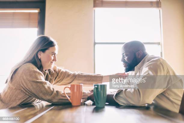Mixed race couple at home at the room dining table