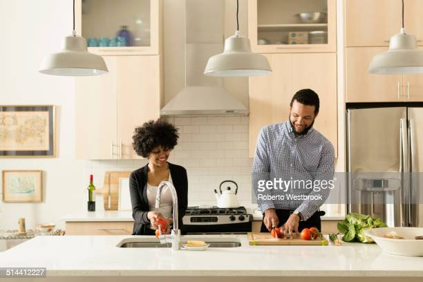 Mixed race couple cooking together in kitchen