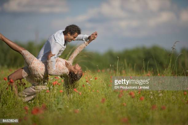 Mixed race couple dancing in field of flowers