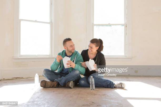 Mixed race couple eating takeout on floor of new home