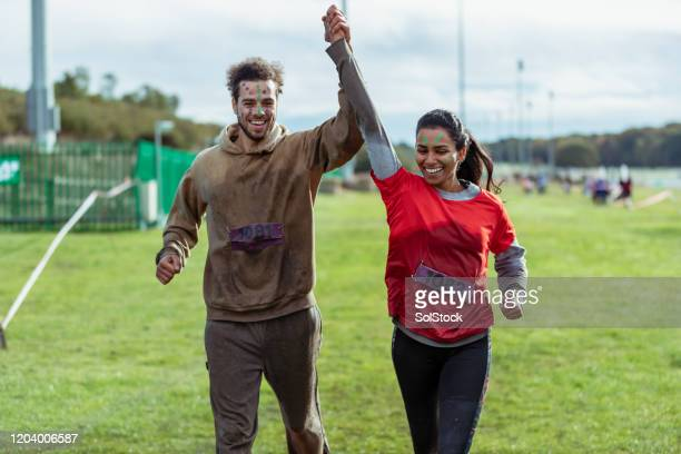 mixed race couple finishing stampede race together - the end stock pictures, royalty-free photos & images