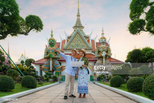 mixed race couple happy tourists to travel on they holidays and holding travel map and pointing in wat arun temple in bangkok, thailand - famous place imagens e fotografias de stock
