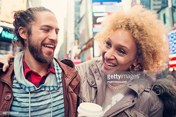 Mixed race couple laughing outdoors in city street.