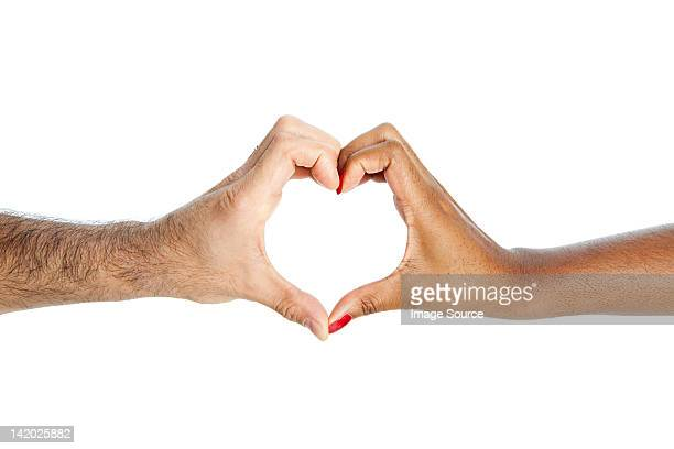 Mixed race couple making heart shape with hands