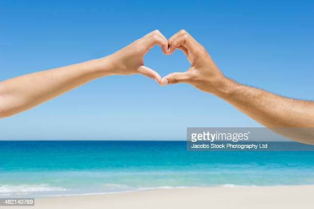 Mixed race couple making heart-shape with hands on beach