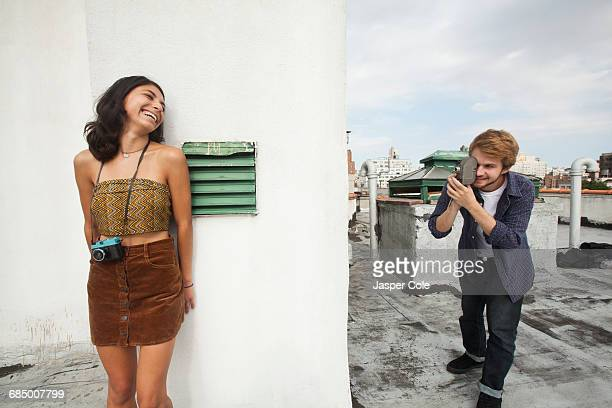 Mixed Race couple playing on rooftop with video camera