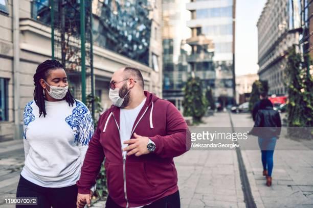 マスクで大気汚染に抗議する混合人種カップル - お面 ストックフォトと画像