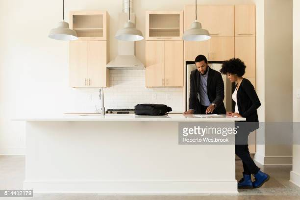 Mixed race couple reading paperwork in new house