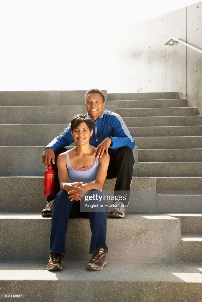Mixed race couple resting on steps after exercise : Stock Photo