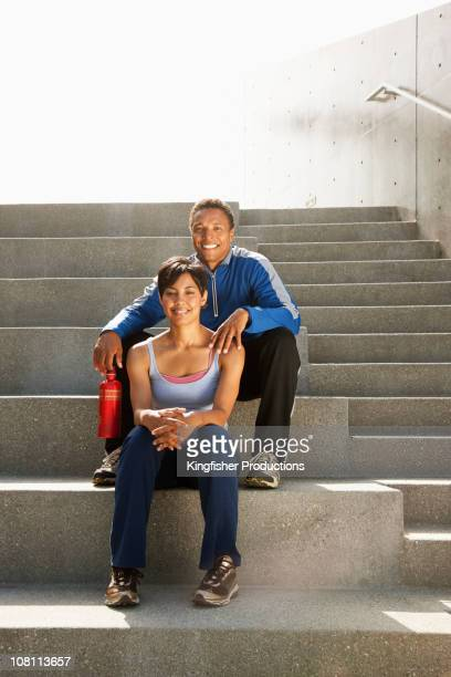 Mixed race couple resting on steps after exercise