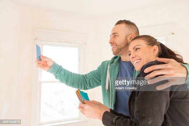 Mixed race couple selecting color swatches in new home