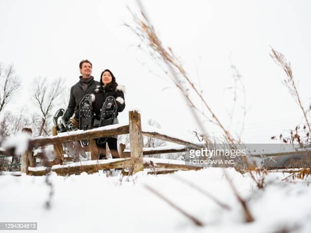mixed race couple snowshoeing in winter - wintersport stock pictures, royalty-free photos & images