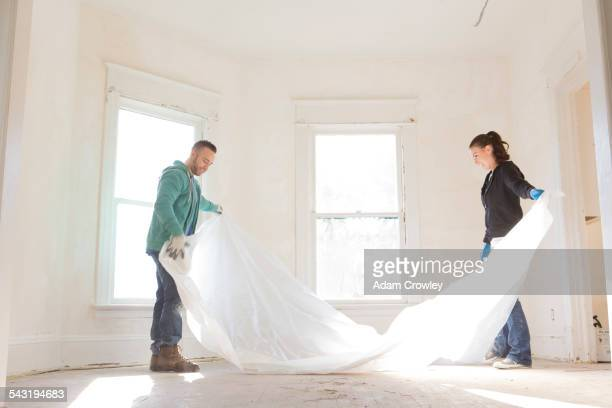 Mixed race couple spreading tarp in new home