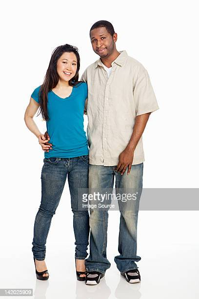 Mixed race couple standing against white background