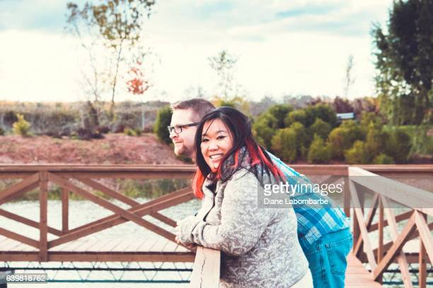 a mixed race couple standing on a bridge in a park - chubby asian woman stock pictures, royalty-free photos & images