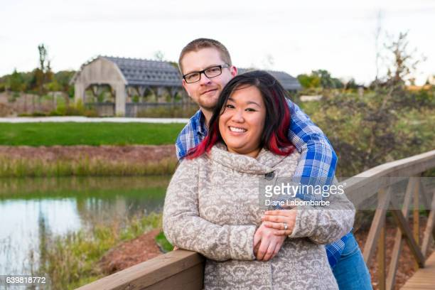 A Mixed Race Couple Standing On A Bridge In A Park