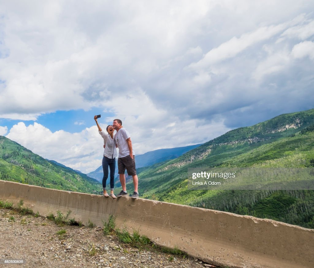Highway 133 from McClure Pass in Summer with a beautiful dramatic sky, an Asian Woman and Caucasian Male take a selfie standing on a concrete road barrier with the Rocky Mountains as a backdrop.