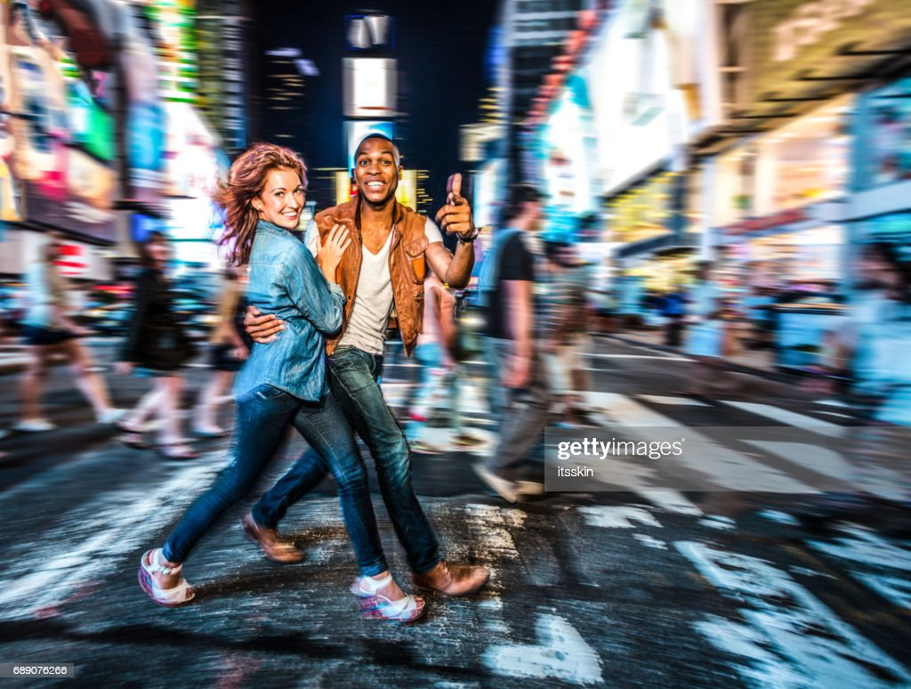 Mixed race couple walking around in New York City, pedestrian crossing : Stock Photo
