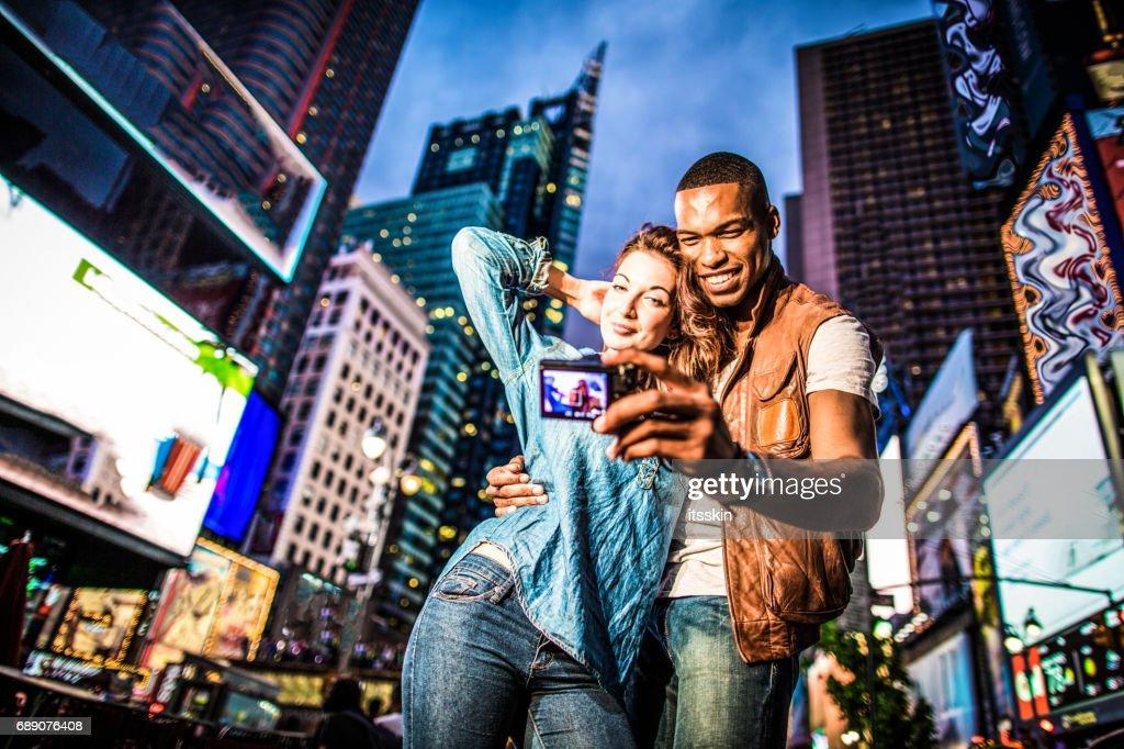 Mixed race couple walking around in New York City, taking selfies : Stock Photo