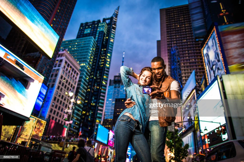 Mixed race couple walking around in New York City, taking selfies : Stock Photo