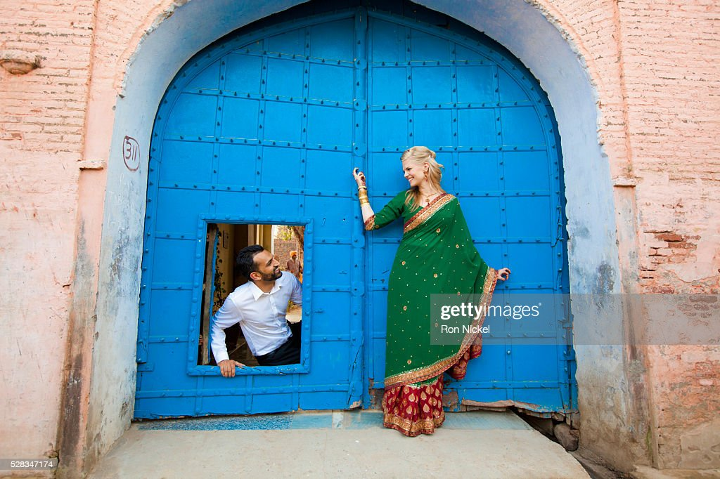 A mixed race couple with her wearing a sari at a doorway with large blue doors; ludhiana punjab india