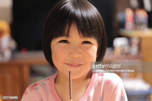 mixed race cute little girl in close up with cocolate cookie stick - saitama prefecture stock pictures, royalty-free photos & images