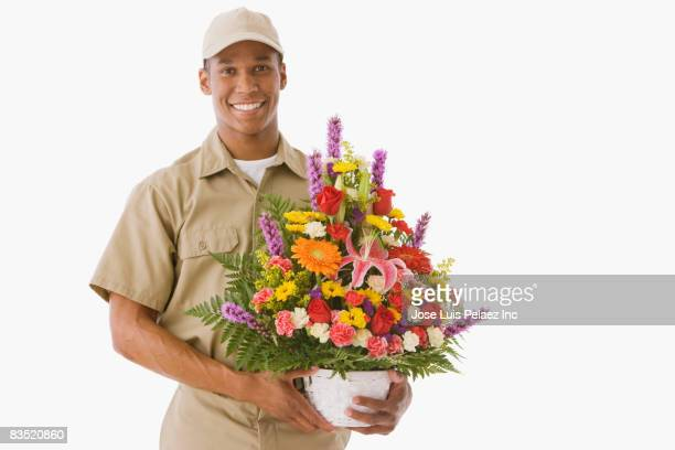 Mixed race delivery man holding bouquet of flowers