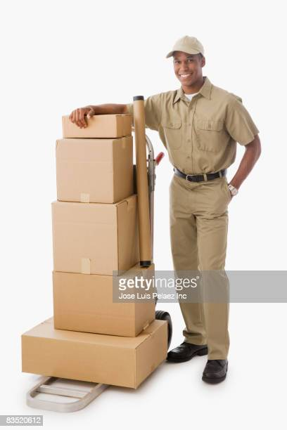 Mixed race delivery man with stack of boxes