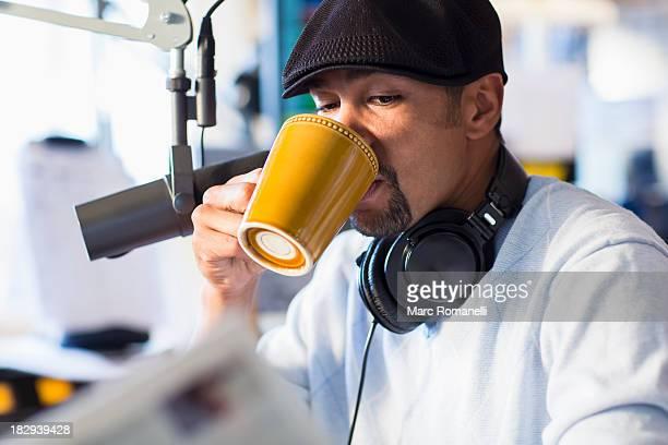 Mixed race disc jockey drinking cup of coffee in studio