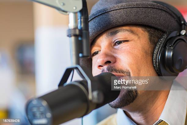 Mixed race disc jockey talking into mic in studio