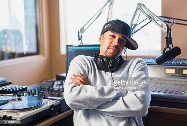 Mixed race disc jockey with arms crossed in studio
