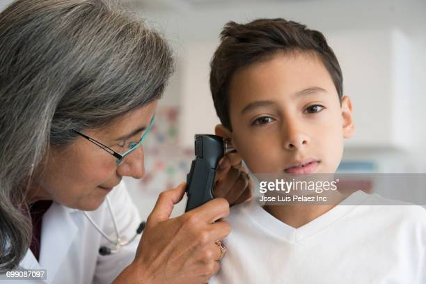 Mixed Race doctor checking ear of patient