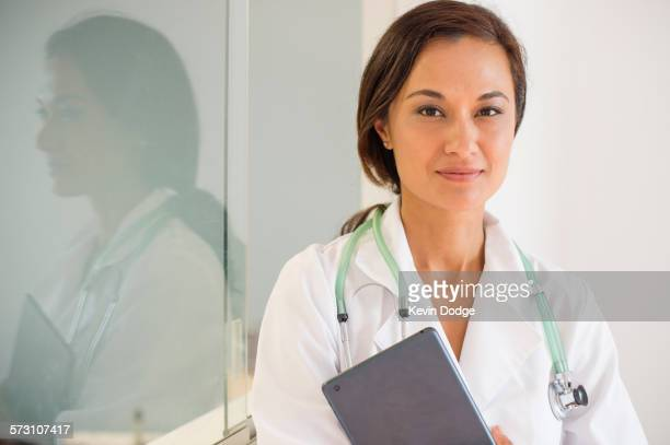 Mixed race doctor holding digital tablet